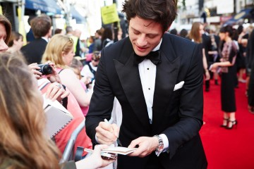 Supporting Actor nominee James Norton signs an autograph on the red carpet. Make up by MAC