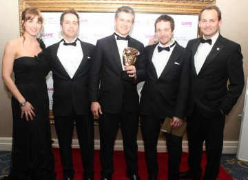 Gaëlec Simard with team, plus presenters Gemma Atkinson and Ben 'The Stig' Collins, with their BAFTA for exhilarating action adventure Assassin's Creed Brotherhood. (Pic: BAFTA/Steve Butler)
