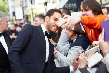 Royce Pierreson shares a selfie with a fan outside London's Theatre Royal
