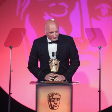 Dan Reed accepts the award for Director: Factual at the British Academy Television Craft Awards in 2015