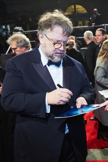 Guillermo del Toro signing autographs on the red carpet