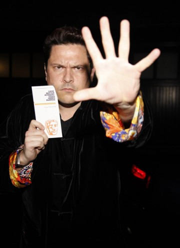 Strategy Award presenter, Dom Joly, battles his way past the waiting press into the Game British Academy Video Games Awards.