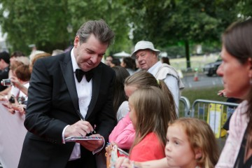 Downton Abbey star Brendan Coyle signs autographs for some young fans.