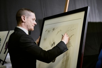 Jack O'Connell signs an awards poster backstage at London's Royal Opera House