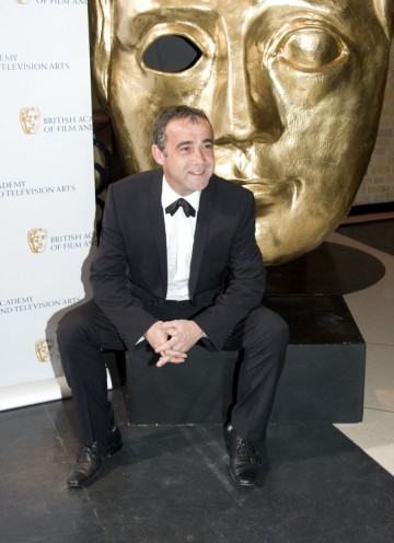 The Coronation Street actor grabs a seat by a BAFTA mask before the show. (Pic: BAFTA/Chris Sharp)