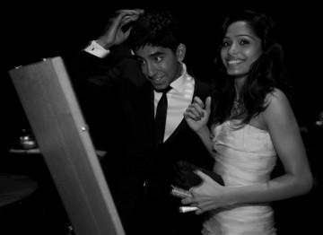 Dev Patel and Freida Pinto, stars of Slumdog Millionaire, prepare to present the Costume Design category on stage (Greg Williams / Art+Commerce).