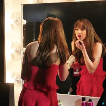 Getting camera ready: Dakota Johnson applies the finishing touches backstage at London's Royal Opera House