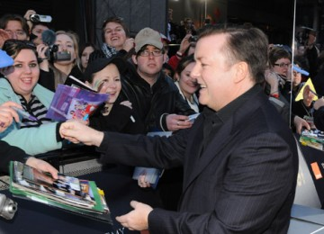Comedian Ricky Gervais signs autographs for film fans on the red carpet.