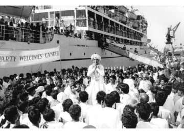 Relcutantly, a garlanded Gandhi (Ben Kingsley) stands on a box provided by those who have organised his welcome home from South Africa.