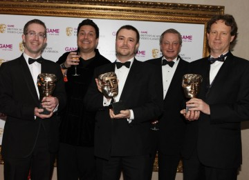Evan Wells and Christophe Balestra celebrate Empire: Total War's BAFTA in the Strategy category with comedian Dom Joly (BAFTA/Steve Butler).