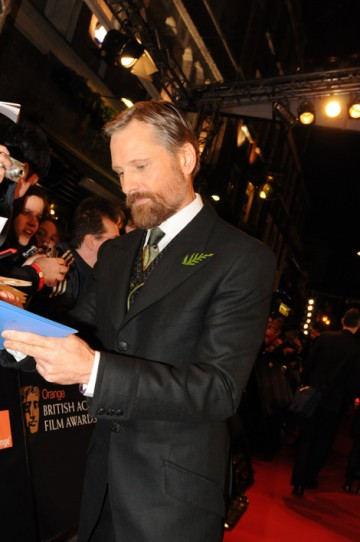 Eastern Promises star Viggo Mortensen signs autographs on the red carpet.