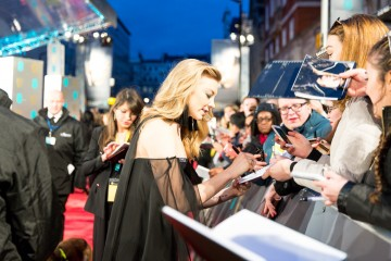 Natalie Dormer signs autographs on the BAFTA red carpet