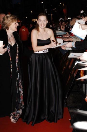 Nominee Kate Winslet signs autographs on the red carpet (BAFTA / Richard Kendal).