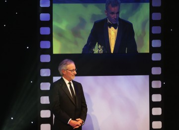 Steven Spielberg watches Daniel Day-Lewis make his acceptance speech.