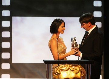 Will Wright receiving the Albert R. Broccoli Britannia Award for Worldwide Contribution to Entertainment from Olivia Munn.