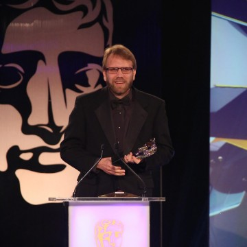 A member of the Hearthstone: Heroes of Warcraft development team accepts the award for Multiplayer at the British Academy Games Awards in 2015