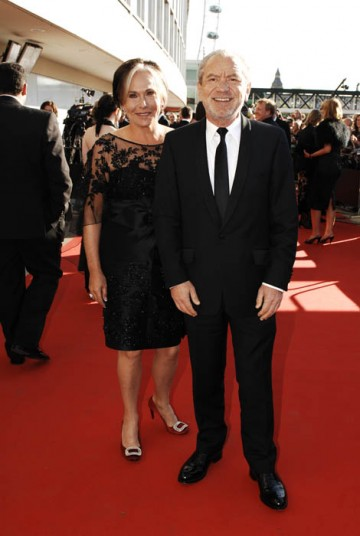 Sir Alan Sugar smiles for the red carpet cameras as he arrives at the Television Awards with his wife Ann (BAFTA / Richard Kendal).