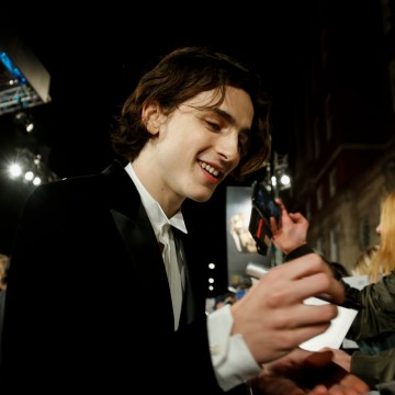 Timothée Chalamet signs an autograph for a fan