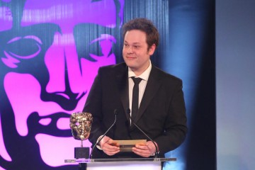 Mike Bithell presents the award for Original Property at the British Academy Games Awards Ceremony in 2015