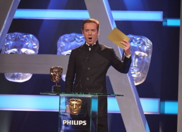 Actor Damien Lewis holds up the winner's envelope for the Supporting Actress category.