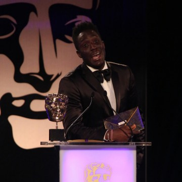 Andy Akinwolere presents the award for Family at the British Academy Games Awards in 2015
