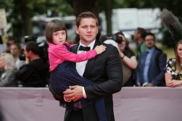 Allen Leech holding his on-screen daughter Fifi Hart on the red carpet at the BAFTA Downton Abbey Tribute event.