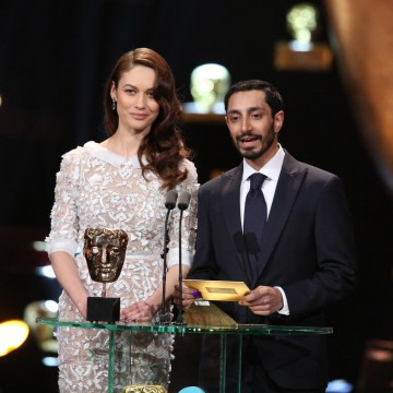 Riz Ahmed and Olga Kurylenko present the award for Costume Design at the 2016 EE British Academy Film Awards