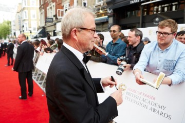 Scripted Comedy nominee Harry Enfield signs autographs on the red carpet