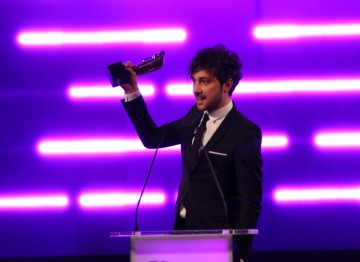 TV Presenter Alex Zane accepts the BAFTA for Debut Game on behalf of the winning team behind Insanely Twisted Shadow Planet.