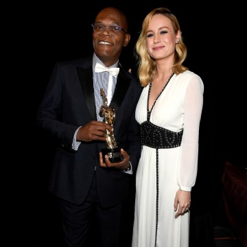 Samuel L. Jackson holds his award and poses with presenter Brie Larson.
