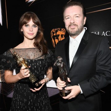 Honorees Felicity Jones and Ricky Gervais pose with their Britannia Awards onstage.