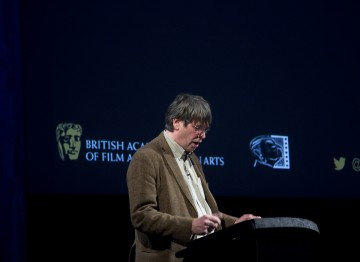 Nik Powell introduces Paul Greengrass to the stage.