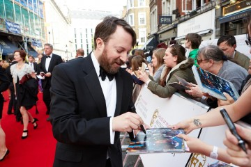 David Mitchell gives an autograph from the red carpet