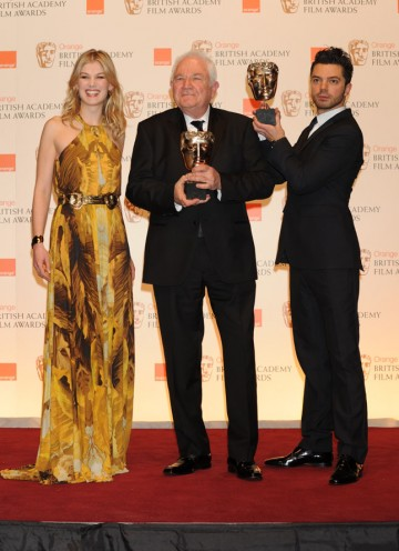 The King's Speech writer David Seidler with presenters Rosamund Pike and Dominic Cooper. Cooper is holding Seidler's earlier BAFTA for Outstanding British Film. (Pic: BAFTA/ Richard Kendal)