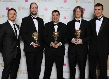 "Presenters Warren Brown (l) and Pete Williamson (r) with winners Mark Healey, David Smith and Pete Smith. The jury praised the game's new editor tools which ""takes user generated content from a simple 'level' to a full game."""