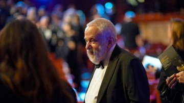 BAFTA Fellow Mike Leigh arrives in the Royal Opera House Auditorium.