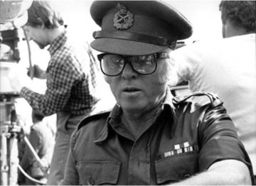 Director Richard Attenborough prepares to film one of the key scenes in New Delhi. So as to keep command of a crowd estimated to number 400,000 he has donned a British Army uniform and will walk behind a re-creation of the Mahatma's funeral cortege.