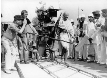 Producer/Director Richard Attenborough, (left) performs a respectful 'pranam', the Indian equivalent of a handshake, for villagers to emulate as Ben Kingsley, who plays the Mahatma, strides past.