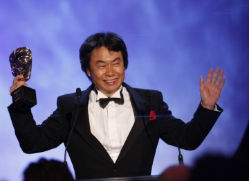 Shigeru Miyamoto celebrates his Academy Fellowship with a cheer on stage at the end of the awards ceremony (BAFTA/Brian Ritchie)