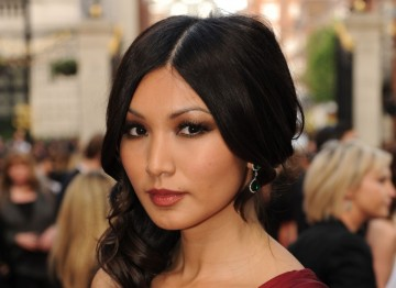 Doctor Who actress Gemma Chan looks beautifully sleek with a sophisticated centre parting, and lightly curled hair draped over one shoulder.