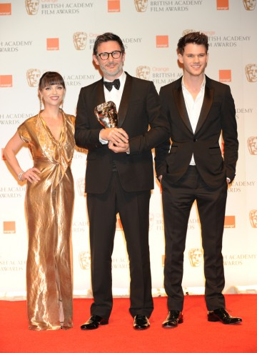 Presenters Christina Ricci and Jeremy Irvine with writer and director Michel Hazanavicius. Christina Ricci wears a gown designed by Givenchy and Jeremy is wearing a suit by Burberry.