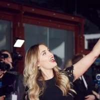 Naomi Kyle takes a picture on the red carpet at the British Academy Games Awards