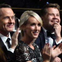 Actor Bryan Cranston, Julia Carey, and honoree James Corden watch the ceremony.