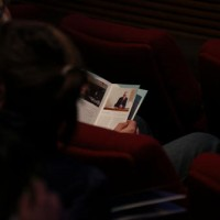 The audience peruse the brochures before the event begins.