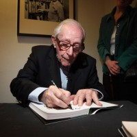 Gilbert signs his memoirs compiled over the course of seven decades working in the film industry.