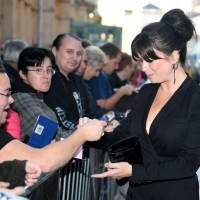 Eve Myles signs autographs for fans on the red carpet