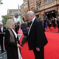 Downton Abbey creator Julian Fellowes being interviewed on the red carpet.