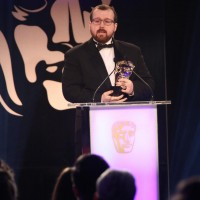 A member of the Far Cry 4 development team accepts the award for Music at the British Academy Games Awards Ceremony in 2015